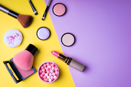 Makeup products and decorative cosmetics on color background flat lay. Fashion and beauty blogger concept. Top view. Copy space