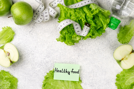 Healthy food. Green apple, lettuce salad, bottle of water, measuring tape on white background. Dieting, slimming, healthy eating concept. Top view, copy space