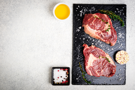 Raw beef steak and ingredients on cutting board. Raw meat on white concrete background. Top view. Copy space Stock Photo