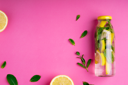 Detox fruit infused water, citrus fruits and mint leaves on pink background. Flat lay summer background with summer drink. Top view. Copy space Stock Photo