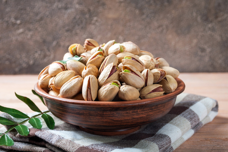 Pistachios nuts in bowl. Pistachio with leaves. Healthy food, snacks, vegetarian food. Copy space