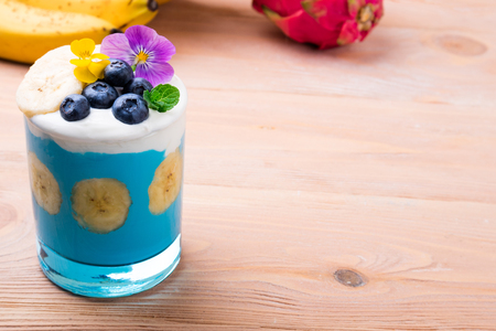 Tropical smoothie with banana fruits, blueberries and flowers on wooden background. Healthy smoothie dessert. Healthy food, vegetarian, diet concept. Copy space