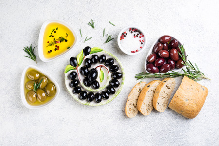Ciabatta bread, olives, oil, herbs and spices on white background. Mediterranean snacks. Top view