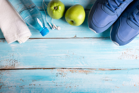 Flat lay sport shoes, bottle of water, apples, towel and earphones on blue background. Sport equipment. Healthy lifestyle, sport and diet concept. Copy space, top view