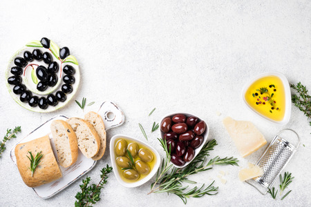 Ciabatta bread, olives, cheese, oil, herbs and spices on white background. Mediterranean snacks. Top view, copy space