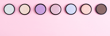 Cosmetics products for makeup  eyeshadow on pink background flat lay. Minimal composition. Fashion and beauty blogging concept. Long web format Stock Photo