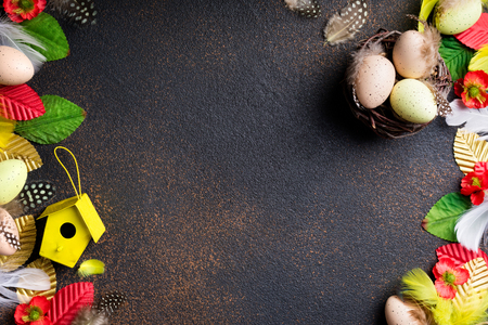Easter composition. Easter eggs, nest with eggs, flowers, feathers and easter decorations on aged stone background. Top view, copy space Stock Photo