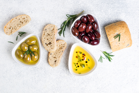 Mediterranean snacks. Ciabatta bread, olives, oil, herbs and spices on white background. Top view Stock Photo