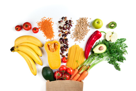 Healthy food background. Healthy vegetarian food in paper bag pasta, vegetables and fruits on white. Shopping food concept. Top view Stock Photo