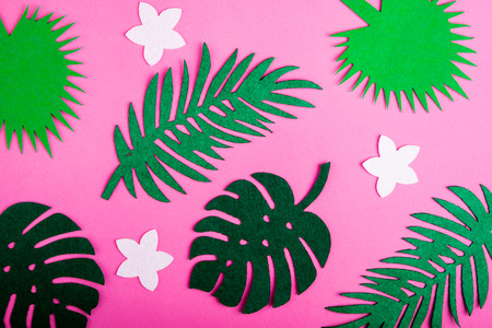 Abstract summer background. Summer trendy background with palm leaves and flowers on pink. Top view