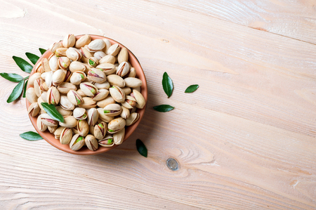 Pistachios nuts in bowl. Pistachio background. Healthy food, snacks, vegetarian food. Copy space Stock Photo