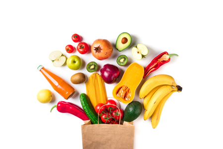 Healthy food background. Healthy food in paper bag pasta, vegetables and fruits on white. Shopping vegetarian food supermarket concept. Top view Stock Photo