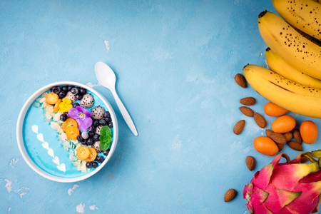 Blue smoothie bowl with fruits, berries, nuts and flowers. Tropical healthy smoothie dessert. Healthy food, vegetarian, diet concept. Top view. Flat lay