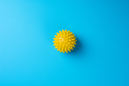Spiky massage ball on blue background top view. Self massage, healthy, wellness and reflexology therapy concept. Copy space