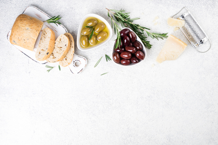 Ciabatta bread, olives, cheese, oil, rosemary herb on white background. Mediterranean or italian snacks. Top view, copy space Stock Photo - 115147319