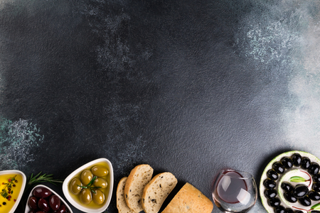 Mediterranean snacks with olives, red wine, ciabatta bread, oil, herbs and spices on black stone background. Appetizer gourman food. Copy space, top view