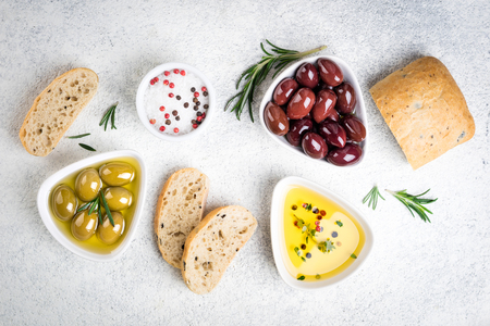 Mediterranean snacks. Ciabatta bread, olives, oil, herbs and spices on white background. Top view Zdjęcie Seryjne