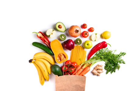Healthy food background. Healthy food in paper bag pasta, vegetables and fruits on white. Shopping food, vegetarian concept. Top view