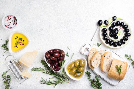 Ciabatta bread, olives, cheese, oil, herbs and spices on white background. Mediterranean snacks. Top view. Copy space Archivio Fotografico - 115147331