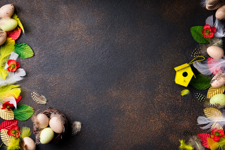 Easter composition. Easter eggs, nest with eggs, flowers, feathers and easter decorations on aged stone background. Top view, copy space Archivio Fotografico - 115147334