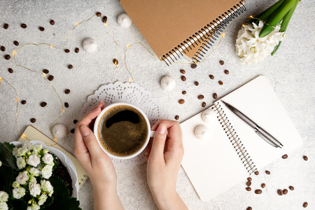 Flat lay feminine background with coffee cup, notebooks and flower hyacinth. Female hands holding coffee cup. Cozy weekend at home concept. Top view Stock Photo - 115147341
