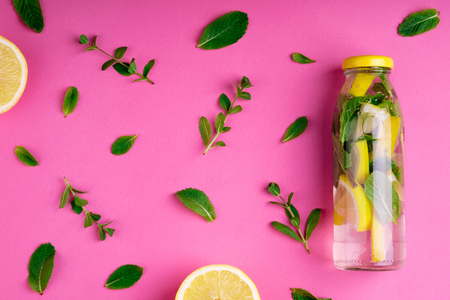 Bottle of tropical water on pink background. Detox fruit infused water, citrus fruits and mint leaves. Top view, flat lay, copy space Zdjęcie Seryjne