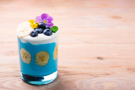 Tropical smoothie with banana fruits, blueberries and flowers on wooden background. Healthy smoothie dessert. Healthy food, vegetarian, diet concept. Copy space Archivio Fotografico - 115147346