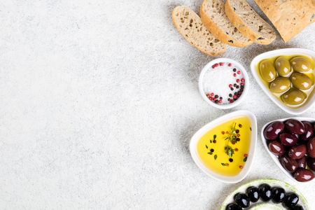 Ciabatta bread, olives, cheese, oil, herbs and spices on white background. Mediterranean snacks. Copy space. Top view Zdjęcie Seryjne