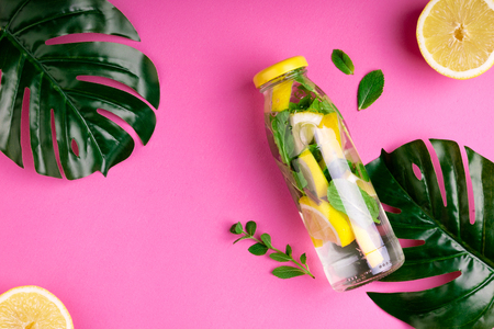 Monstera leaves and bottle tropical water on pink background. Detox fruit infused water, citrus fruits and mint leaves. Top view, flat lay, copy space Archivio Fotografico - 115147351