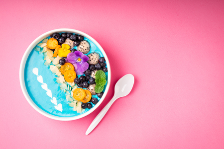 Blue smoothie bowl with fruits, berries, nuts and flowers on pink background. Tropical healthy smoothie dessert. Healthy eating, vegetarian, diet concept. Top view