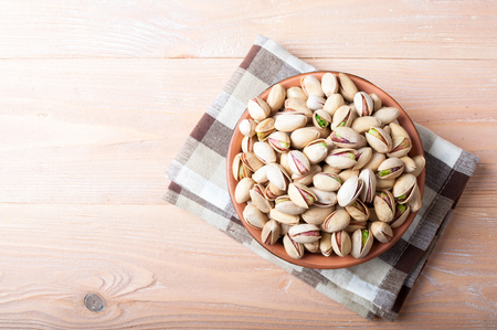 Pistachios nuts in bowl. Pistachio background. Healthy food, snacks, vegetarian food. Top view, copy space