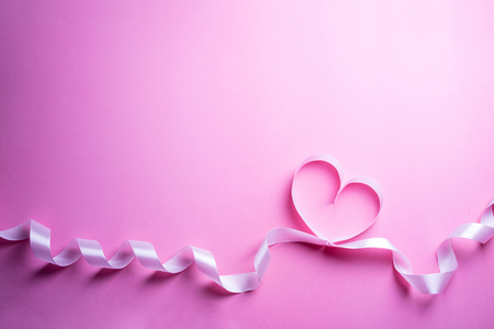 Valentines Day background with pink heart. Heart shape from ribbons. Top view