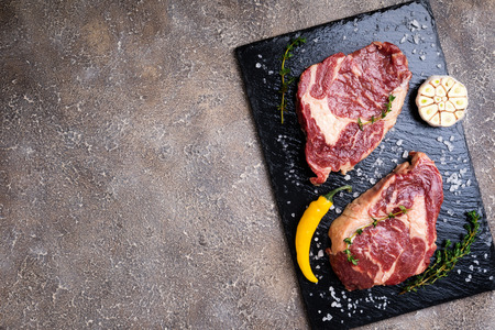 Raw beef steak and ingredients on cutting board. Raw meat on concrete background. Top view Zdjęcie Seryjne