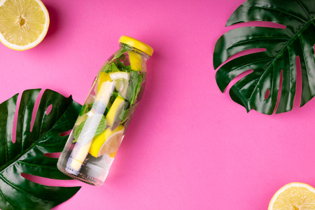 Bottle tropical water and monstera leaves on pink background. Detox fruit infused water, citrus fruits and mint leaves. Top view, flat lay. Copy space Stock Photo - 115147410