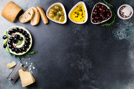 Mediterranean snacks. Olives, ciabatta bread, cheese, oil, herbs and spices on black stone background. Appetizer gourman food. Copy space, top view Zdjęcie Seryjne