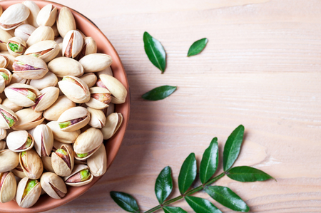 Pistachios nuts in bowl. Pistachio with leaves. Healthy food, snacks, vegetarian food. Top view, copy space