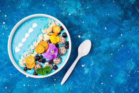 Blue smoothie bowl with fruits, berries, nuts and flowers. Tropical healthy smoothie dessert. Healthy food, vegetarian, diet concept. Top view. Copy space