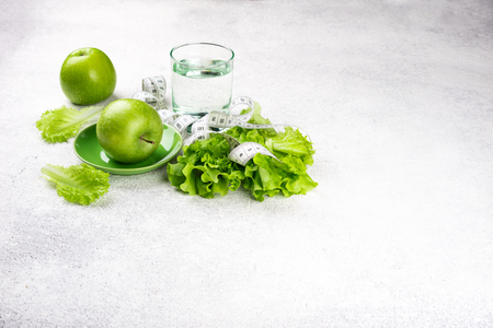 Healthy eating. Green apple, lettuce salad, glass of water, measuring tape. Dieting, slimming, weight loss and meal planning concept. Top view and copy space