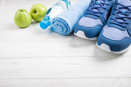 Flat lay sport shoes, bottle of water, apples, towel and earphones on white wooden background. Sport equipment. Healthy lifestyle, sport and diet concept. Copy space Zdjęcie Seryjne