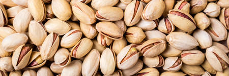 Pistachios nuts background. Pistachio texture. Long web format for banner Archivio Fotografico - 115147442