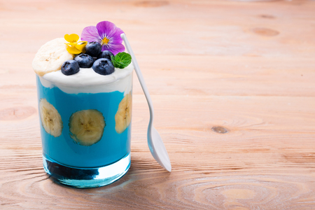 Healthy smoothie with banana fruits, blueberries and flowers on wooden background. Tropical smoothie dessert. Healthy food, vegetarian, diet concept. Copy space