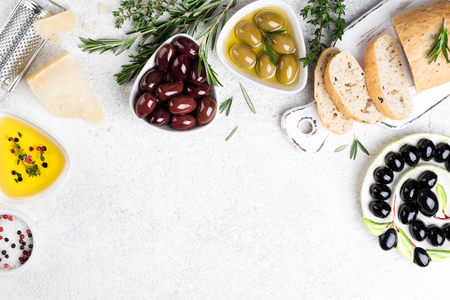 Mediterranean snacks. Ciabatta bread, olives, cheese, oil, herbs and spices on white background. Copy space, top view Stock Photo - 115147445