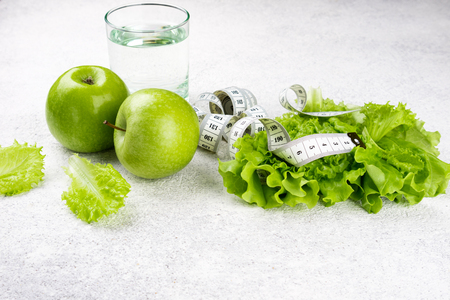 Healthy eating. Green apple, lettuce salad, glass of water, measuring tape. Dieting, slimming, weight loss and meal planning concept Stock Photo - 115147449