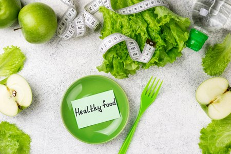 Healthy eating. Green apple, lettuce salad, water bottle, measuring tape. Dieting, slimming, weight loss and meal planning concept. Copy space and top view Zdjęcie Seryjne