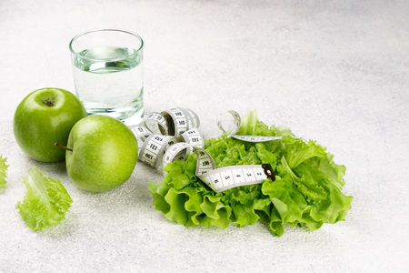 Healthy eating and diet background. Green apple, lettuce salad, glass of water, measuring tape. Dieting, slimming, weight loss concept. Top view. Copy space Archivio Fotografico - 115147455