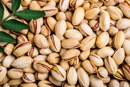 Pistachio background. Nuts. Pistachio texture with leaves. Top view Imagens