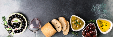 Olives, red wine, ciabatta bread, oil, herbs and spices on black stone background. Mediterranean snacks. Appetizer gourman food. Copy space, top view Stock Photo - 115147459