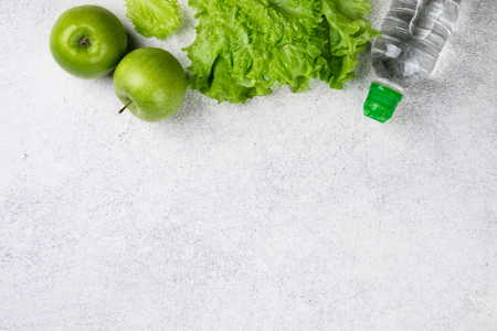 Healthy eating. Green apple, lettuce salad water bottle on white background with copy space. Dieting, slimming and weigh loss concept Archivio Fotografico - 115147466