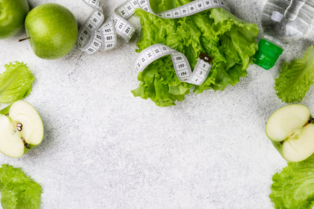 Healthy eating. Green apple, lettuce salad, water bottle, measuring tape. Dieting, slimming and weigh loss concept. Copy space and top view Stock Photo - 115147468