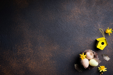 Easter composition. Easter background nest with eggs, flowers and easter decorations on aged stone background. Top view. Copy space